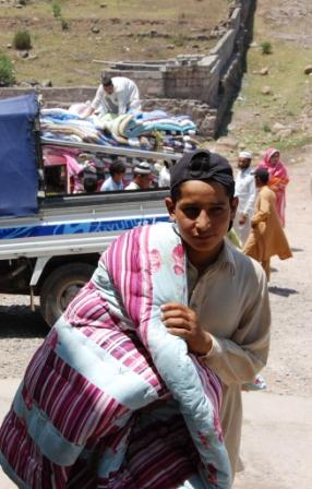 A young boy from Fatipur helps deliver mats to the building where his family has been welcomed to stay