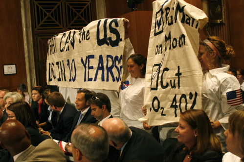 "Seven climate activists dressed as astronauts stood up during yesterday's Environment and Public Works Senate hearing and unfurled bannars that read: ""What can the US do in 10 years?"" and ""Put a man on the moon (check); cut co2 40% (dotted-line-check)."""