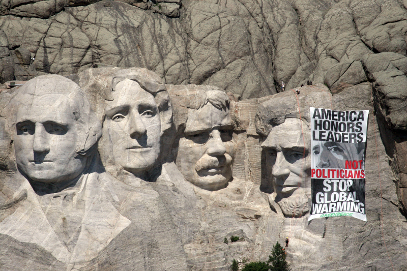 Twelve members of Greenpeace were arrested for hanging a banner on South Dakota's Mount Rushmore yesterday to protest global warming as the G-8 summit in Italy begins.