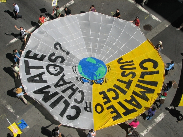 "The Mobilization for Climate Justice led a blockade of four lanes of traffic in San Francisco with a parachute-shaped banner that read ""Climate Justice or Climate Chaos."" The action was directed against Chevron and the corporate-driven US climate bill."