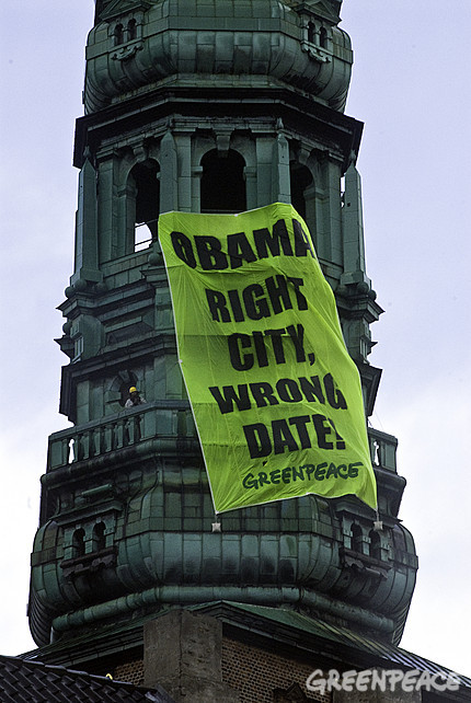 "Greenpeace activists hung a huge banner from the St Nicholas Church Tower in Copenhagen on Friday that read ""Obama: Right city, wrong date"". It was meant as a reminder to Obama, who was in town to lobby for Chicago as the 2016 Olympic Games host, that he needs to return in December for the UN Climate Summit."