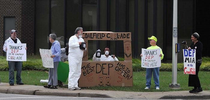 "A dozen people gathered in Kanawha City, West Virginia outside the Department of Environmental Protection on Tuesday to protest the agency's leniency in granting surface mining contracts. They set up a ""coalfield cool-ade"" stand offering up jugs of black liquid to represent the slurry water coming from the faucets of those who live near coal mining."
