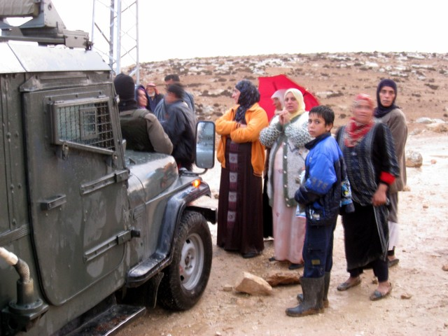 Residents of At-Tuwani Village step into the path of an Israeli military jeep that had arrived to oversee dismantling and confiscation of the village's new electrical pylons. Israeli occupation authorities declared the area a closed military zone and threatened to arrest Palestinians and internationals present.