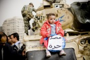 "A child sitting on an army tank in Tahrir Square, with a banner that reads ""Egypt is free"" on January 29, 2011. By Hossam el-Hamalawy, via Flickr."