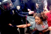 "During Occupy Wall Street's March 24 ""Let Freedom Spring"" march against police brutality, a protester's shirt is torn as police arrest her."