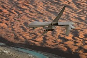 An MQ-1 Predator unmanned aircraft, armed with Hellfire missiles, flies over southern Afghanistan. Photo by Charles McCain via Flickr.