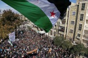 yria independence flag flies over a large gathering of protesters in Idlib, Syria in March 2012. Photo by Freedom House via Flickr.