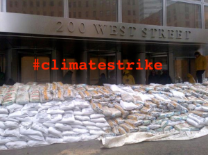 "Meme of Goldman Sachs Tower behind sandbags, accompanying the article ""Climate Strike: All Storms Lead to Wall Street."" (Occupy Theory)"