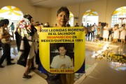 Mercedes Moreno holds a sign with a picture of her son, José Leonidas Moreno, who disappeared in 1991. (WNV/Mario Marlo)