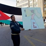 A man holds a sign at Jan. 18 protest in Amman, Jordan. (WNV/Omar Alkalouti)