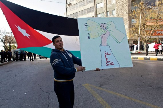 A man at the Jan. 18 protest in Amman, Jordan, holds a sign depicting the map of Jordan being squeezed. (omaralkalouti.com/©Omar Alkalouti)