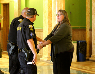 Linda Kenoyer being arrested during the third day of sit-ins at the Montana Capitol. (Coal Export Action / Rae Breaux)
