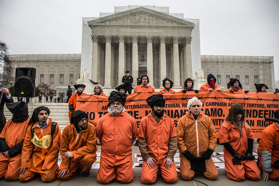 On January 11, Witness Against Torture activists pose in front of the U.S. Supreme Court, which is covered in a false facade for repairs. (Flickr/Justin Norman)