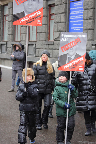 "Children carrying signs with the word ""Shame"" stamped over pictures of Russian politicians who voted for the anti-adoption law. (Flickr / Sergey Kukota)"