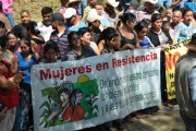 "The Communities in Resistance hold a banner that reads ""Women in Resistance"" during a confrontation with mining company agitators. (GHRC)"