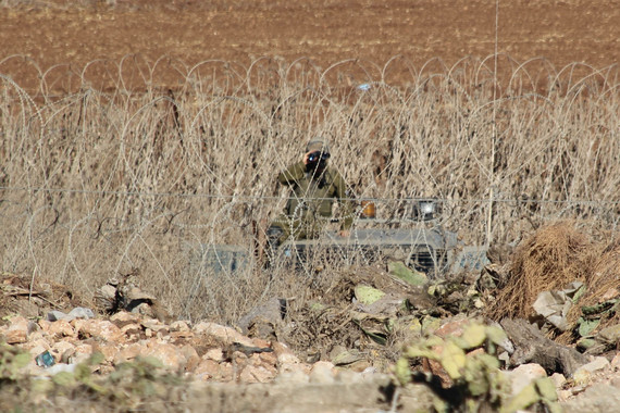 At the edge of the West Bank village of Faqqua, an Israeli soldier watches from the other side of the Green Line. (Left in Focus/Bryan MacCormack)