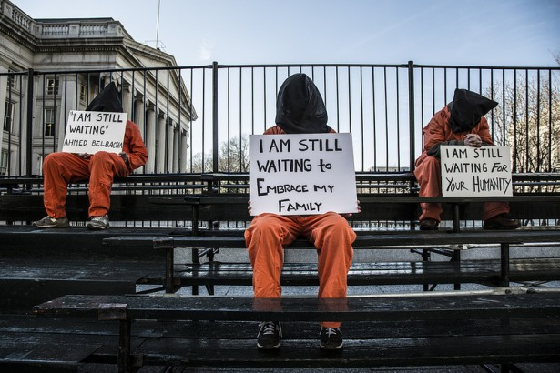 Perched on the bleachers erected for President Barack Obama's second inauguration, members of Witness Against Torture hold signs in the iconic orange jumpsuits. (WNV/Justin Norman)