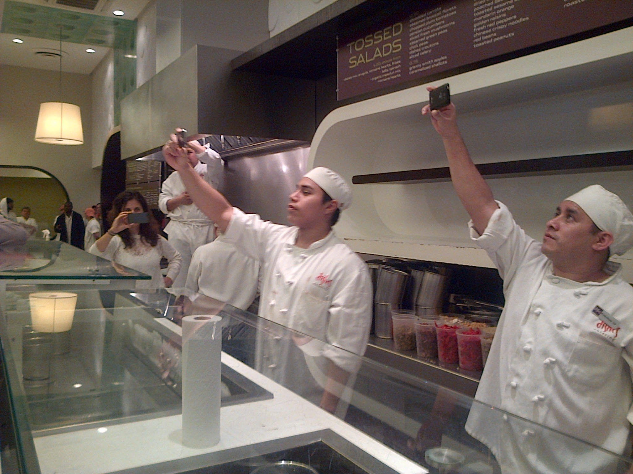 On shift workers at Dishes film the action on their camera phones. (WNV/Laura Gottesdiener)