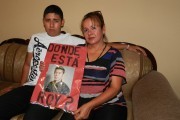 "Richie Rivera (left) and his mother Letty Hidalgo hold a protest sign that reads, ""Where is Roy?"" (WNV/Osvaldo Hernandez)"