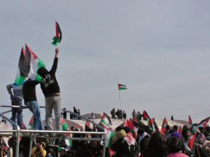 Protester holds up a Palestinian flag at the Bab al-Shams encampment in January. (WNV/Creede Newton)
