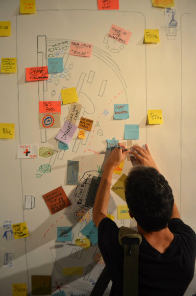 An Occupy Wall Street activist contributes to a map of Zuccotti Park created after Sunday's Participatory Walking Tour of the Financial District. (Stacy Lanyon)
