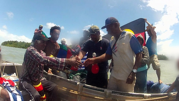 Kevin Buzzacott and Ronny Kareni giving the 'sacred water' from the Lake Eyre springs to Frans Kapissa and Eliezer Awom from the National Federal Republic of West Papua. (WNV/West Papua Freedom Flotilla collection)