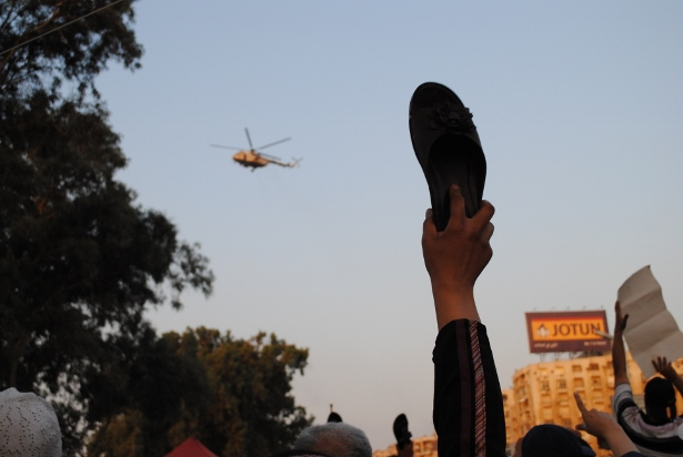 A Egyptian protester raises a shoe to the sky as a military helicopter flies overhead. (WNV/Jihad Abaza)
