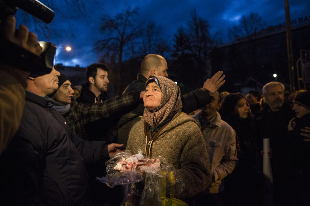 An elderly woman presents discarded pieces of raw meat during a protests in Sarajevo on February 8, 2014, outside the city's municipal building. It sustained heavy damage after protesters attacked and set fire to it. (WNV/Jodi Hilton)