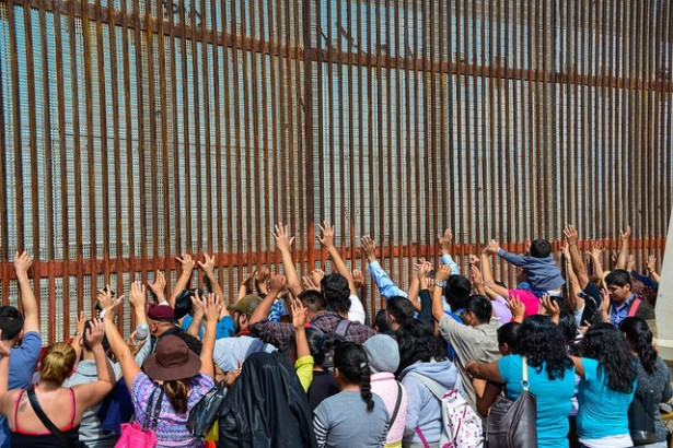 Families who have been deported and are now returning to the United States during a mass border crossing rally at the U.S.-Mexico wall. (Flickr/Steve Pavey 2014)