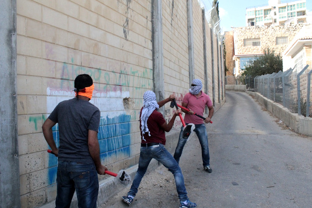 Palestinians hammer at the wall. (WNV/Andrew Beale)