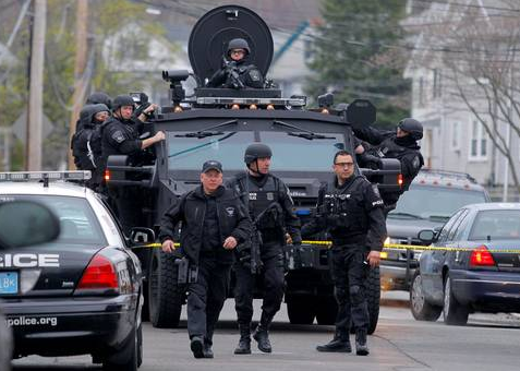 SWAT teams enter a suburban neighborhood to search an apartment for the remaining suspect in the Boston Marathon bombings in Watertown. (Independent)