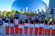 """Dressed as Guantanamo detainees, activists in Chicago call for the closure of the prison and an end to torture in front of """"The Bean"""" in Chicago's Millennium Park on May 23. (Chicago Coalition to Shut Down Guantanamo)"""