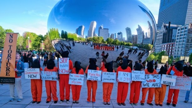 "Dressed as Guantánamo detainees, activists in Chicago call for the closure of the prison and an end to torture in front of ""The Bean"" in Chicago's Millennium Park on May 23. (Chicago Coalition to Shut Down Guantanamo)"