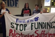 Jewish Voice for Peace members unfurl a banner at the Friends of IDF office in New York City. (Facebook)