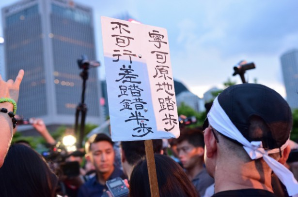 "A protest sign says: ""To rather stay where we are than make a step in the wrong direction."" (WNV / Elaine Yu)"