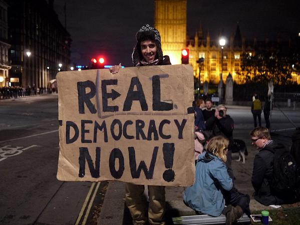 A protester involved with Occupy Democracy outside of parliament in London. (Twitter/JJ Wyatt)