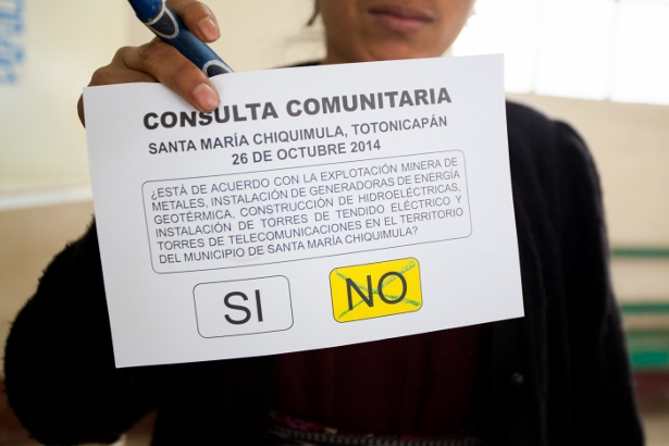 A woman holds up her ballot to show that she voted against mining projects within the territory. (WNV/Jeff Abbott)