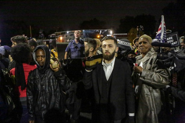 The reflection of a police officer can be seen in the Glass Casket carried by protesters in Ferguson. (heartacheandpaint.com)