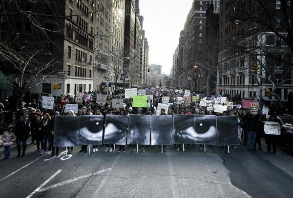 The enlarged eyes of Eric Garner and other young black men were carried during the Millions March in New York City on December 13. (Twitter/JRart)