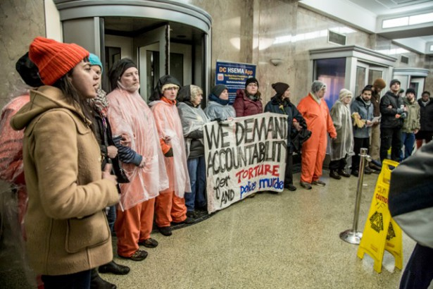 Witness Against Torture members demonstrating in the entrance of DC Metro Police headquarters on January 12, 2015.  (WNV/ Justin Norman)