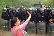Yolanda Oqueli stands in between the Guatemalan National Police and the entrance of the mine as the mining firm KCA arrives with machinery for the El Tambor mine on May 23, 2014. (Guatemalan Human Rights Commission)