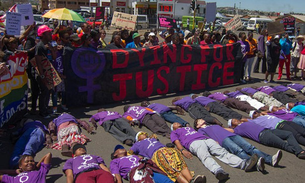 """Soweto Pride 2012 participants protest against violence against lesbians with a """"Dying for Justice"""" banner and T-shirts which read """"Solidarity with women who speak out."""" (Wikipedia / Charles Haynes)"""