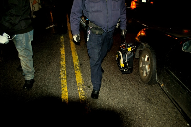 An NYPD officer striding parallel to an East Flatbush anti-police brutality rally carries a portable sound cannon in his arm. (WNV/Peter Rugh)