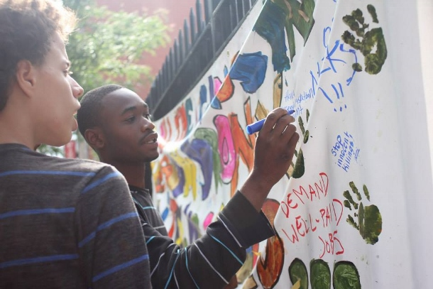 Local youth write on a large banner at a no-cop zone event in the Bronx. (Take Back the Bronx)