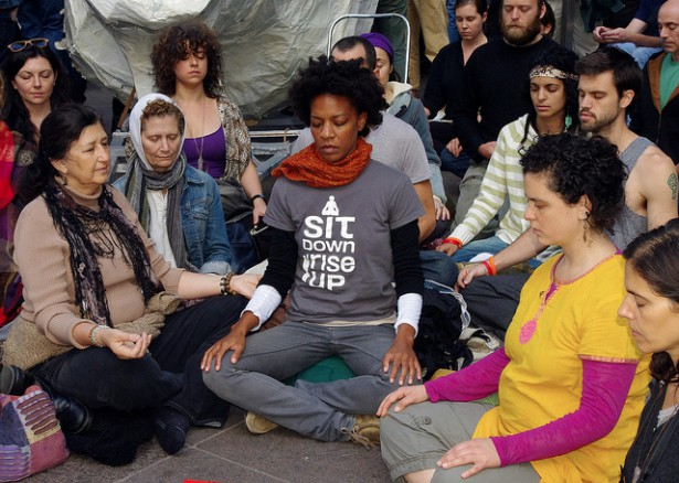 "Leslie Booker, center, in ""Sit Down, Rise Up"" T-shirt meditates with other activists in Zuccotti Park during Occupy. (WNV / Karsten Braaten)"