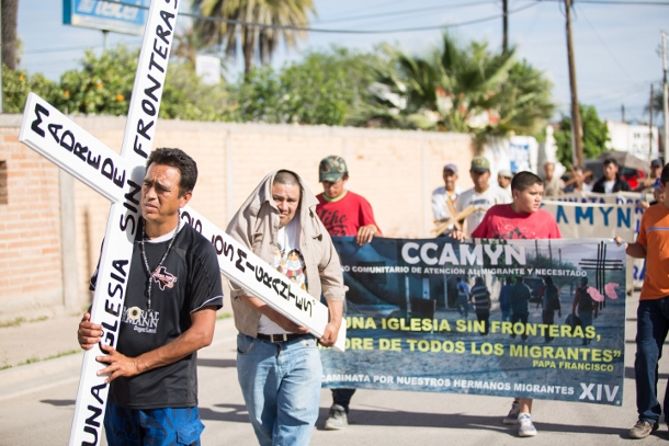 "Two men migrating to the United States lead a march in Altar, Sonora carrying a cross that reads ""a church without borders."" (Left in Focus/Bryan MacCormack)"