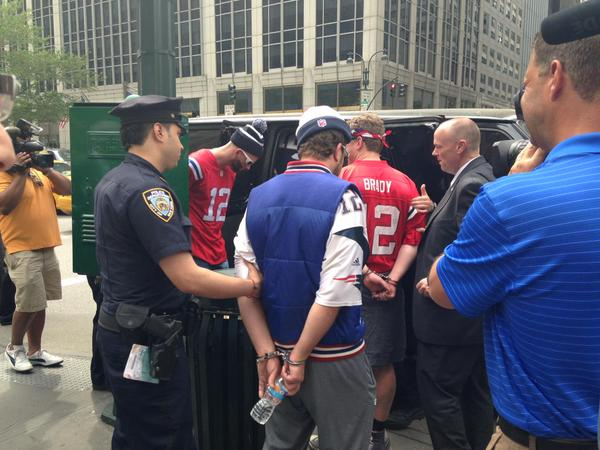 Patriots fans were arrested and taken to Central Booking in New York City on Monday for handcuffing themselves together outside NFL headquarters. (Twitter / Lisa Kraus Edwards)