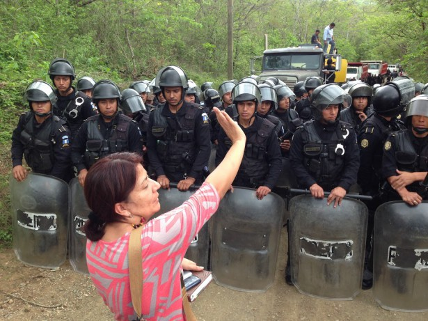 Yolanda Oquelí stands in between the Guatemalan National Police and the entrance of the mine as the mining firm KCA arrives with machinery for the El Tambor mine on May 23, 2014. (Guatemalan Human Rights Commission)