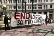 A banner is held at Oscar Grant Plaza as part of the Statewide Coordinated Actions to End Solitary Confinement on March 23. (San Fransisco Bay View)