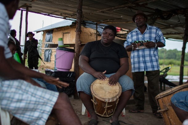Cesar Leonel plays a drum in the center of the Vallecito community, as the three soldiers sit at the periphery of the gathering. (WNV/Jeff Abbott)